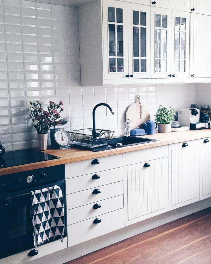 Białe szafki i drewniany blat w skandynawskiej kuchni