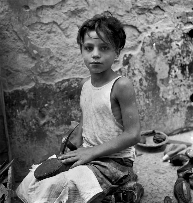 David Seymour  ITALY. Naples. 1948. A little boy apprenticed to an open-air shoemakers' shop.