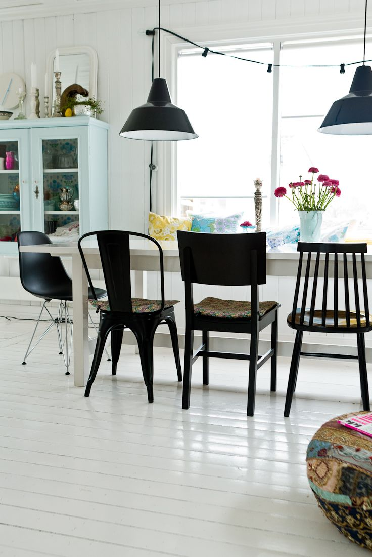 Painted white floors w/ mismatched black chairs/lighting.  Simple and sophisticated at the same time.