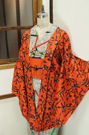 綺麗なスカーレットオレンジに、グラフィティ・アートのようなモダンデザインが織り出された銘仙の長羽織です。