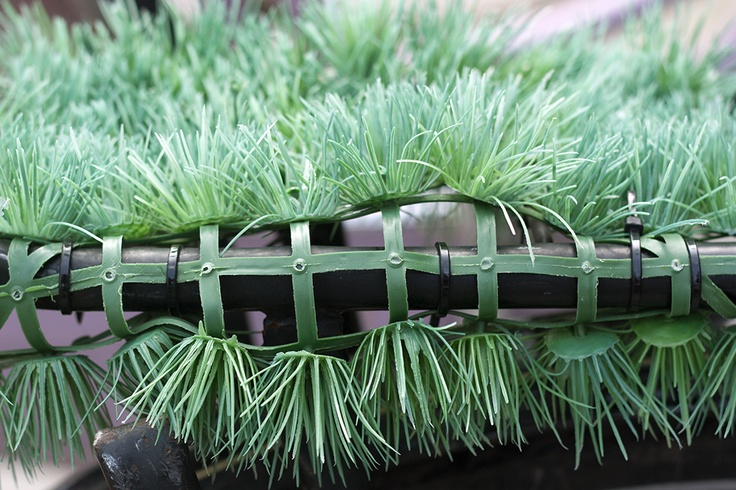 A little plastic mat of grass at the back of a bicycle.