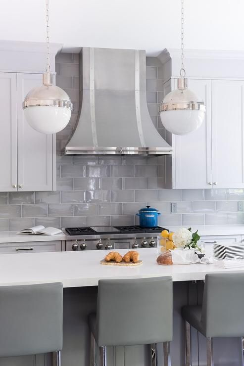 White shaker cabinets paired with white quartz countertops and a gray beveled subway tile backsplash.
