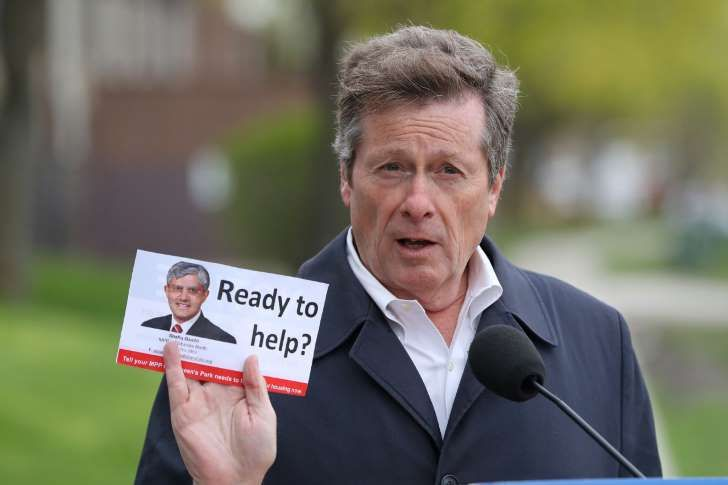 "Mayor John Tory holds a flyer with a picture of Etobicoke North MPP Shafiq Qaadri, demanding that Queen's Park help Toronto tackle a growing community housing repair bill. Last week's provincial budget was ""a big goose egg when it came to social housing repairs,"" the mayor said."