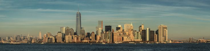Panoramic landscape of New York city as the sun sets for the day from Liberty Island in New York Harbor. Lower Manhattan, also known as Downtown Manhattan, is the southernmost part of the island of Manhattan, and where the city was founded in 1624.  New York, USA.