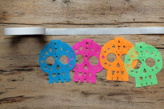 Calavera papel picado free templates and patterns. Cute sugar skull garland with step-by-step photo instructions. How to string up your calavera sugar skulls using masking tape - See the rest here - https://happythought.co.uk/craft-ideas/papel-picado-calaveras