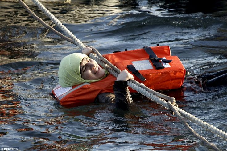 Hanging in there: One desperate refugee woman hangs on a rope having escaped the half-sunk...