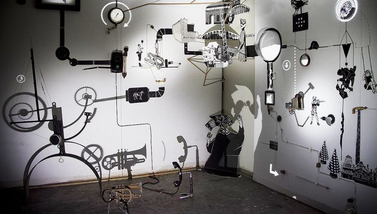"Mécaniques Discursives, or ""mechanical discursive,"" is a work-in-progress art installation that combines Rube Goldberg logic with light, shadows, wooden shapes, found objects, and full motion video."
