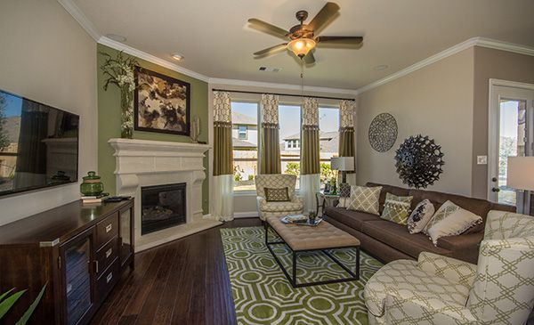 This living room has splashes of green all around, including the fireplace accent wall and the rug and other decor!