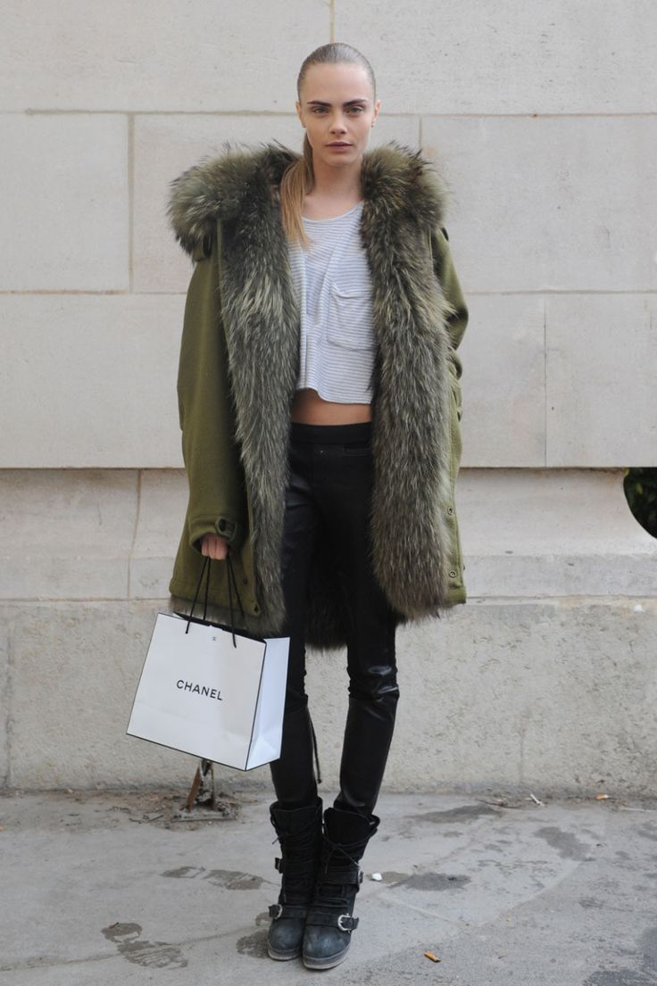 Cara Delevingne StyleChi Army Green Coat Fur Lining Hood Part Leather Black trousers Strappy Biker Boots White Pocket Striped T-Shirt Hair Pulled Back No Make Up Effect
