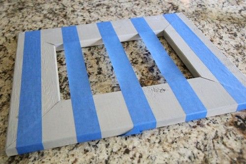 Use tape over picture frames and spray paint to make a striped frame!