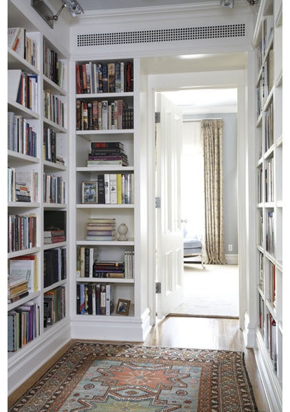 Note that these shelves have artwork lights above them and baseboards at the bottom that coordinate with the rest of the room. This lends a uniform feeling.