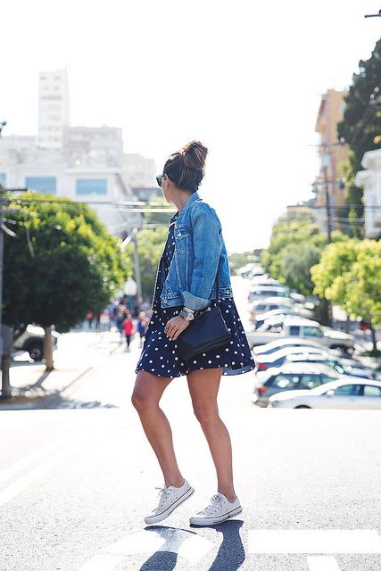 Dotted navy blue romper with a denim jacket and white converse and a messy bun. Yass
