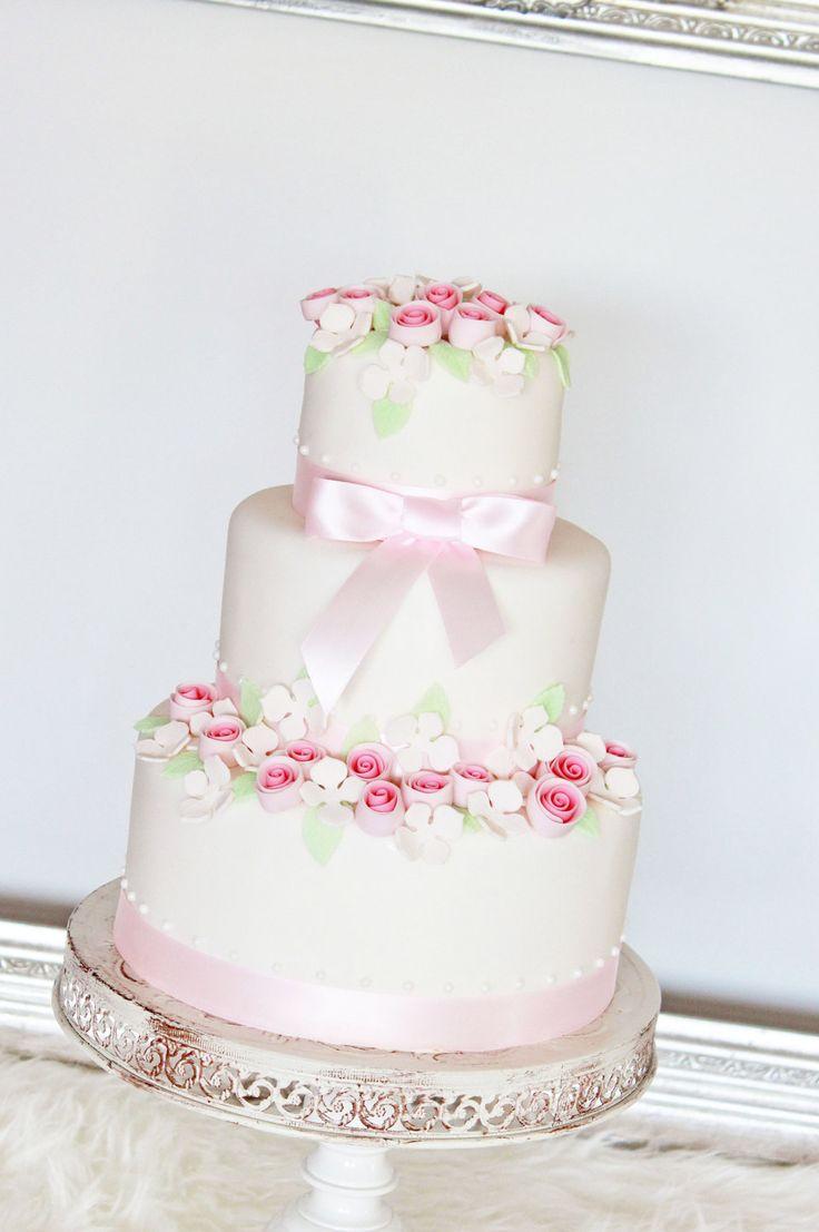 bruidstaart wit met roze bloemen en lichtroze strikken