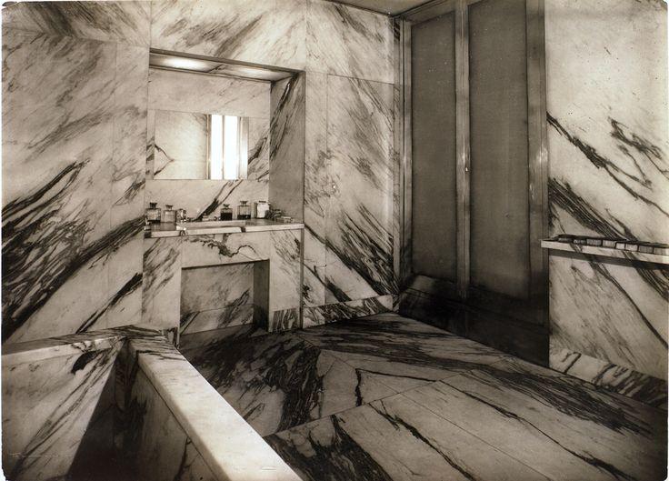 Salle de bains de l'appartement de Jean-Michel Frank, vers 1925. Murs en marbre veiné anthracite, porte en bronze patiné médaille et verre dépoli. Photographie de Man Ray.Fondation Pierre Bergé - Yves Saint-Laurent.