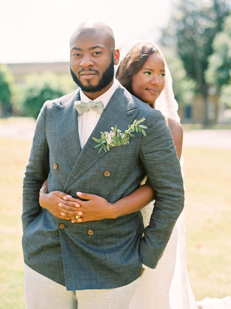 Dapper grey check suit, light green bowtie and leafy buttonhole