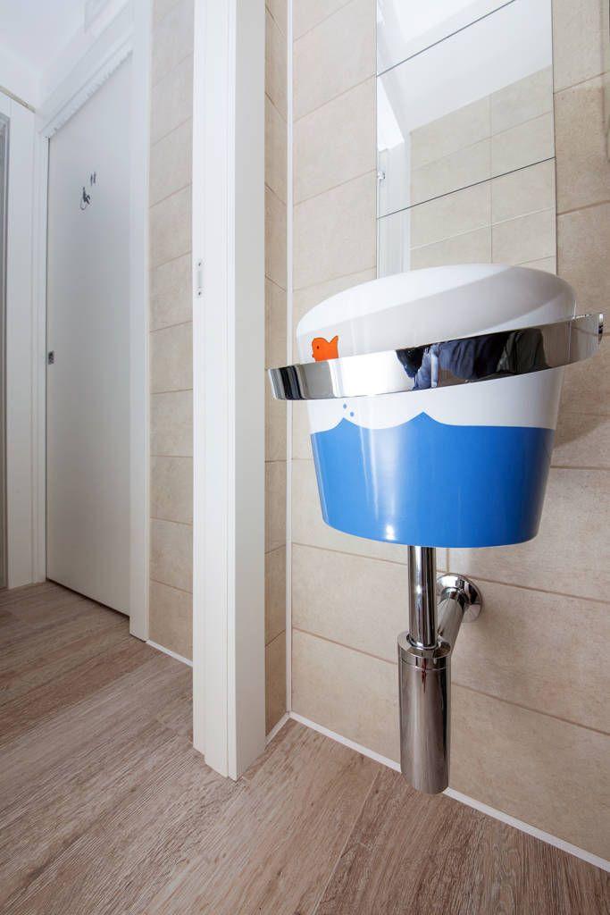 Un piccolo lavabo dalla curiosa forma di secchiello da spiaggia (di STUDIO PAOLA FAVRETTO SAGL - INTERIOR DESIGNER)