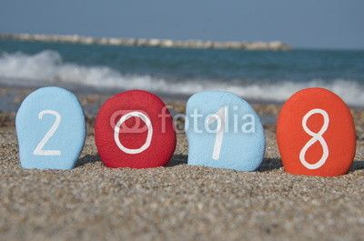 Happy New Year 2018 on colourful stones over the sand