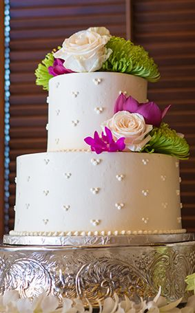 Classic white wedding cake adorned with tropical flowers and tiny Hidden Mickeys