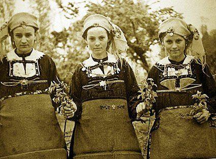 Λαζαρίνες της Λευκοπηγής με την παραδοσιακή τους φορεσιά κρατώντας άνθη. Στην ποδιά της μεσαίας διακρίνονται αντωπά κεντημένα σχέδια, πουλιά και φυτά (Αρχείο ΕΜΑΣ Μέγας Αλέξανδρος Λευκοπηγής)