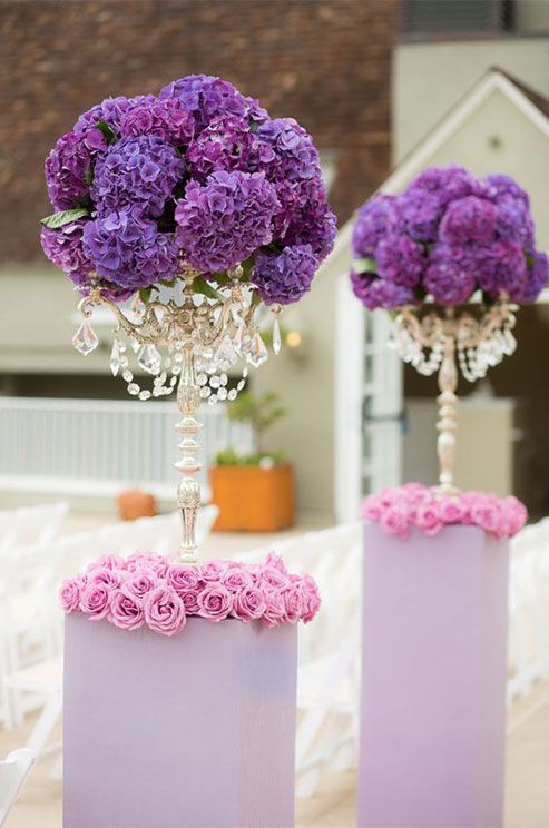 Purple Wedding Inspiration: Clusters of purple hydrangeas and crystals become topiaries when placed atop silver candelabras. http://www.colincowieweddings.com/flowers-and-decor/purple-wedding-flowers