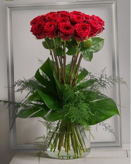 Idylle Rouge: Bouquet haut et serré de grandes roses rouges à gros boutons avec un travail graphique de feuillage.