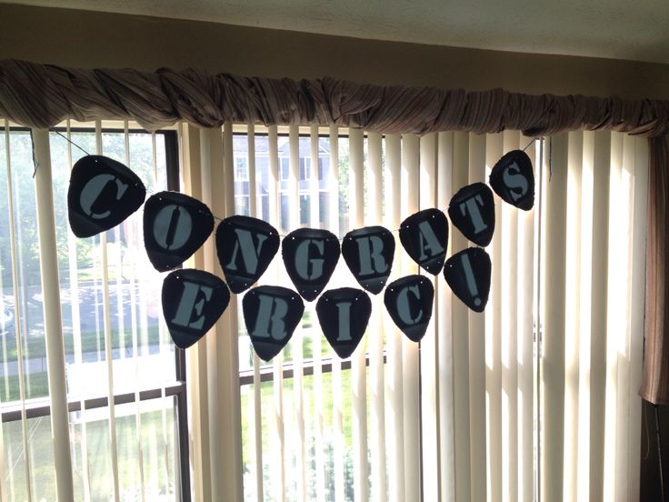 Graduation party banner for the guitar lover! Super easy DIY- cut guitar picks from cardboard, spray paint them your desired colors, and string them through with craft twine. I used a Philips head screwdriver to make the holes.