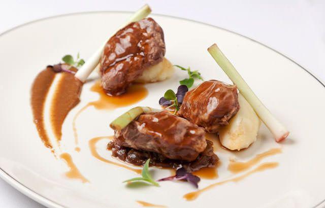 Braised pork cheeks with baby leeks, sultana ragu, mash and caraway jus
