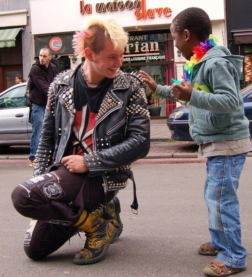 A punk stops during a gay pride parade to allow a mesmerized child to touch his jacket spikes