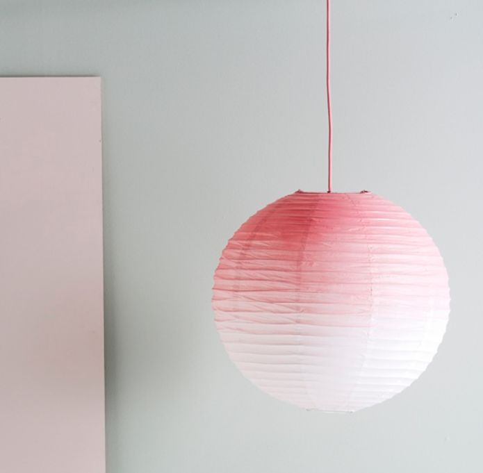 Recreate the look by saturating the top of the lamp with spray paint and allowing the paint to disperse, fading to white. Repeat for the desired effect and finish by spraying the pendant cord pink