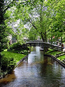 Giethoorn, Netherlands.  This idyllic village has no roads, and the only access is by water over the many beautiful canals or on foot over its wooden arch bridges. The locals use punters to get around and cars have to remain outside the village.  Located in the province of Overijssel, there are 4 miles of canals and farmhouses with thatched roofs dating back to the 18th century.