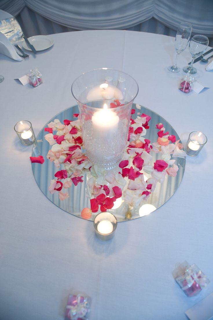 Fresh rose petals surrounding hurricane candle lamp