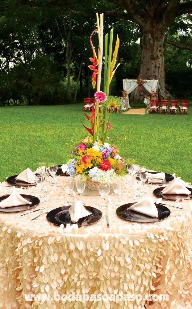 Montaje de mesa, Mantelería conformada por hojas sobrepuestas en todo el mantel, plato base color chocolate, servilletas color crema rodeando un agradable centro de mesa con variedad de flores en vivos colores.