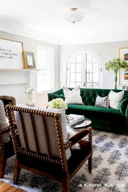 Beautifully appointed transitional living room showcases a stunning emerald green velvet tufted sofa topped with white pillows and facing two brown velvet spindle chairs accented with gray striped pillows lit by a glass and brass flush mount.
