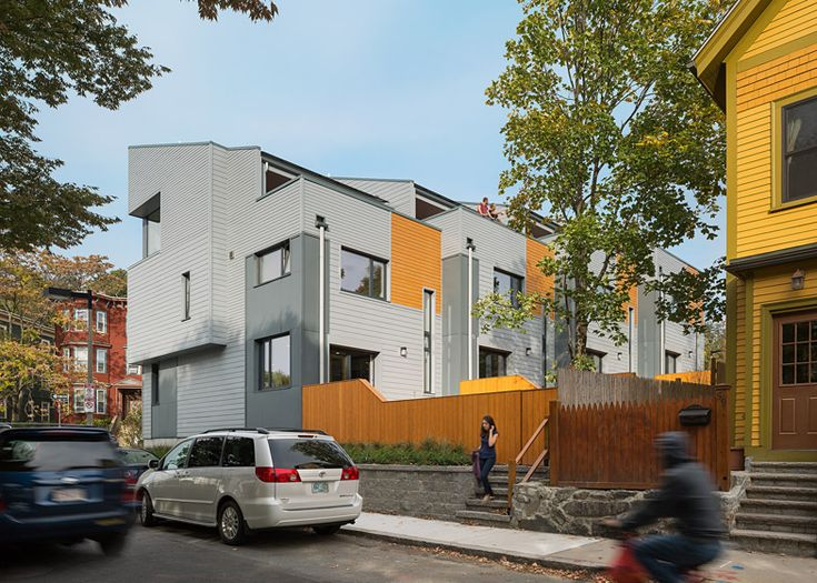 Boston townhouses by ISA produce a surplus of energy  clad in metal and timber panels