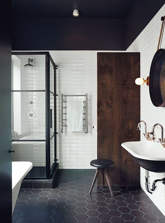 Dark floor tile and shower platform. Black-rimmed shower door. White subway tile.