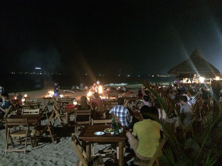 Sailing Club by the beach with bon fire by night