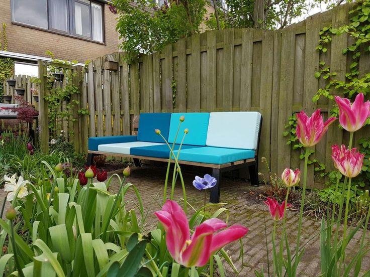 Mooie dag voor het plaatsen van een tuinbank van 2 meter lang. Kussens van Sunbrella stof in mooie frisse kleuren.