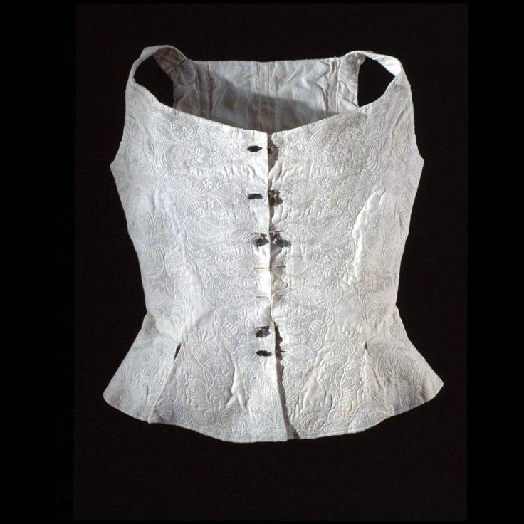 "Woman's waistcoat or jumps, quilted 1720-1750 Origin: Europe L: 20 1/2""; W: (at shoulders) 12 1/2"". White tabby cotton, cord quilted and embroidered with linen; linen lining and tapes for boning. Gift of Anonymous Donors Acc. No. 1971-1566"