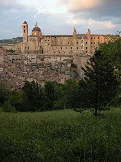 Urbino tényleg ilyen váratlanul, minden átmenet nélkül emelkedik ki a zöld dombok közül a hegytetőn, mint a középkori várak Berry herceg hóráskönyvében. Más középkori olasz városokat modern elővárosok széles sávja veszi körül, de Urbinót Federigo da Montefeltro herceg 15. századi építkezései olyan aránytalanul nagyra szabták, mint a kölyökkutya bundáját, hogy a város azóta sem tudott még teljesen belenőni.