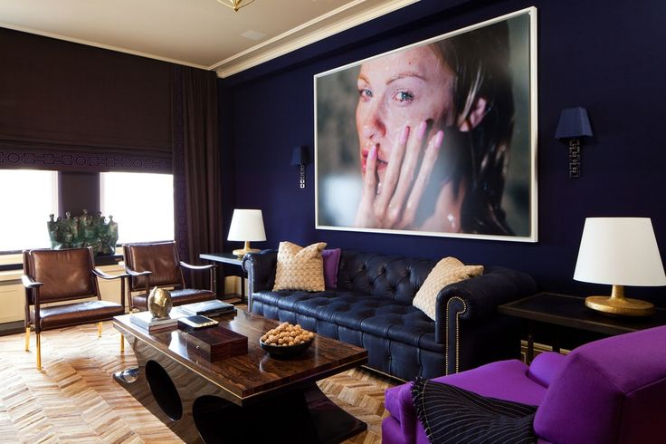 A sultry photograph by Marilyn Minter hangs above a navy chesterfield sofa in the library. The picture is framed by Nisbet's Swank Sconces for The Urban Electric Co. The varying shades of brown and blue used throughout the space bring a richness and dark glamour that is complemented by the lighter tones of the herringbone patterned Kyle Bunting carpet.