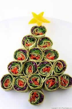 Kerstboom van wraps  Deze kerstboom is gemaakt van opgerolde stukjes wraps. Op het voorbeeld zijn ze gevuld met roomkaas, pesto, stukjes wortel en rode kool en blaadjes spinazie. Maar je kunt natuurlijk nemen wat je wilt. Een plakje van een stervrucht maakt de kerstboom helemaal af.