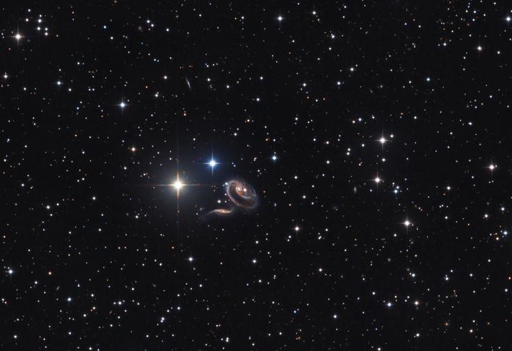 Las estrellas con puntas en primer plano de esta imagen se encuentran dentro de nuestra Vía Láctea. Las dos vistosas galaxias están mucho más allá de la Vía Láctea, a una distancia de unos 300 millones de años luz. El aspecto distorsionado es debido a las mareas gravitacionales que se crean cuando la pareja se ve afectada por las colisiones cercanas. Catalogadas como Arp 273 (también como UGC 1810)