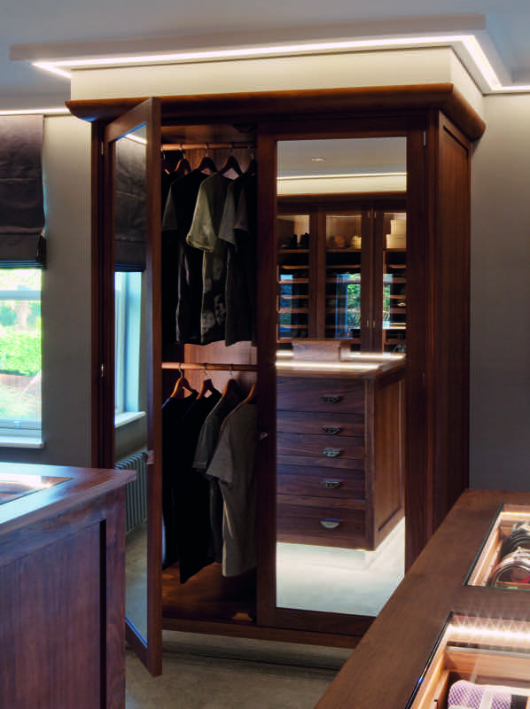 Ceiling and under-cabinet lighting adds ambiance to this perfectly organised Smallbone dressing room