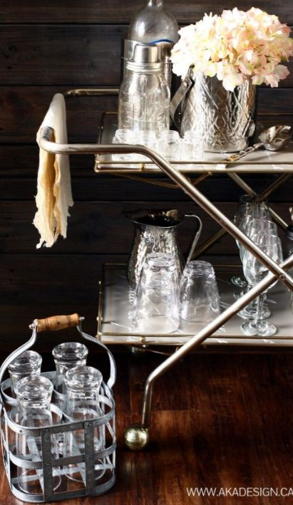 i have a soft spot for silver bar carts and this one had me at hello! so nice with the white accents and all the barware looks great! wine glasses mason jars, rocks glasses, martini shaker, wine chiller