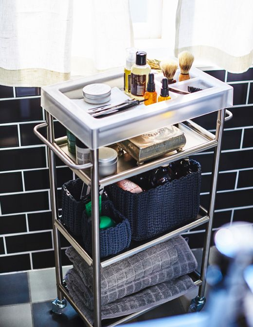 A bathroom utility cart propped with men's grooming products, like shaving equipment and towels.