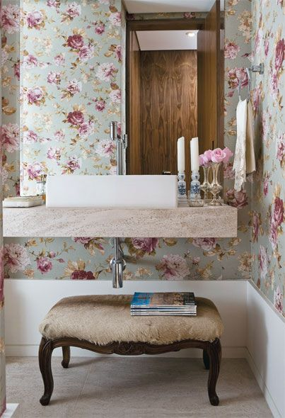 A inspiração do dia é o romantismo. O papel de parede com estampa floral e o banco retrô criam um contraste com a bancada de linhas retas e contemporâneas.
