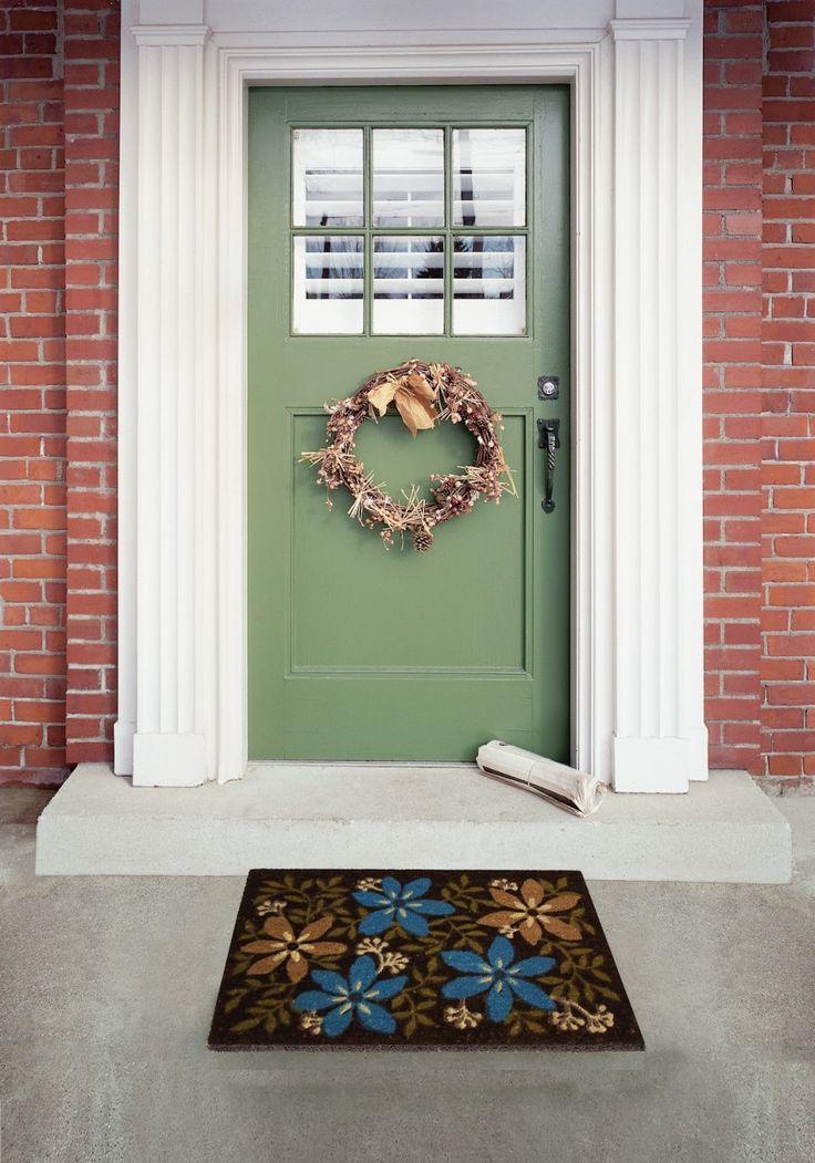 exterior interesting wreath on green front door facing flowery front door mats and concrete flooring