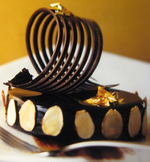 chocolate delice with gold flakes and tempered chocolate swirl