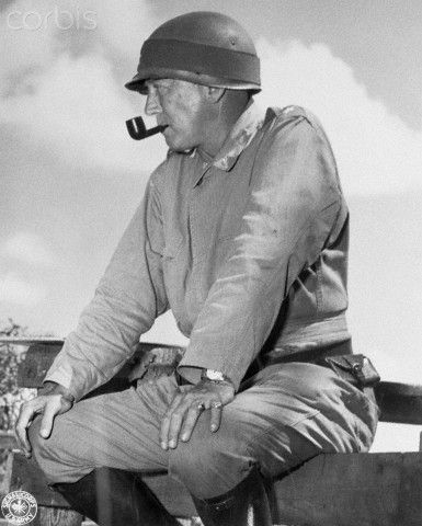Lieutenant General George S. Patton sitting on a fence and smoking a pipe while observing 1941 maneuvers in Louisiana.