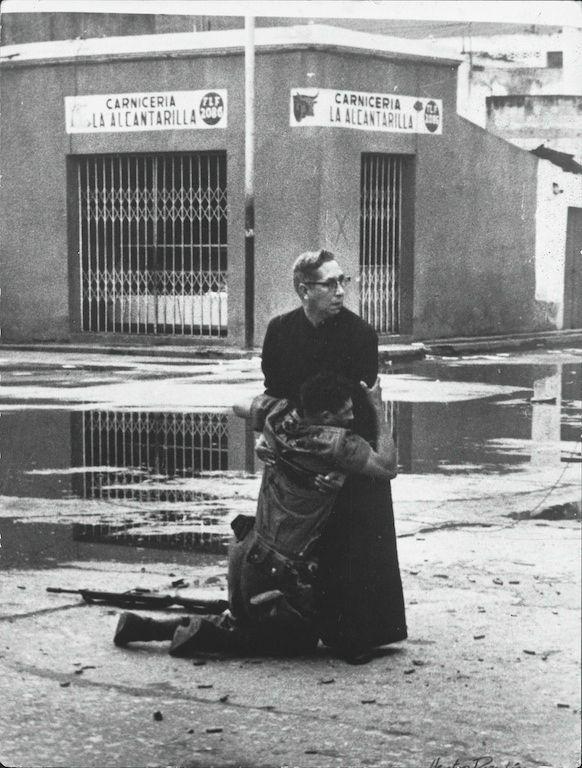 1962年 「Uprising in Venezuela (ベネズエラの暴動)」 ベネズエラのゲリラ組織「民族解放武装勢力」が起こした暴動の中、全身を狙撃兵に撃たれた兵士が司祭に抱かれている写真。
